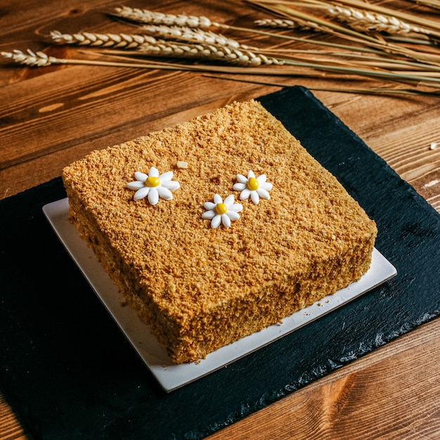 カモミールスクエアで飾られた正面図の蜂蜜ケーキは、茶色の背景に白いプレート菓子の甘さの誕生日の中においしい誕生日ケーキを形成しました 無料写真