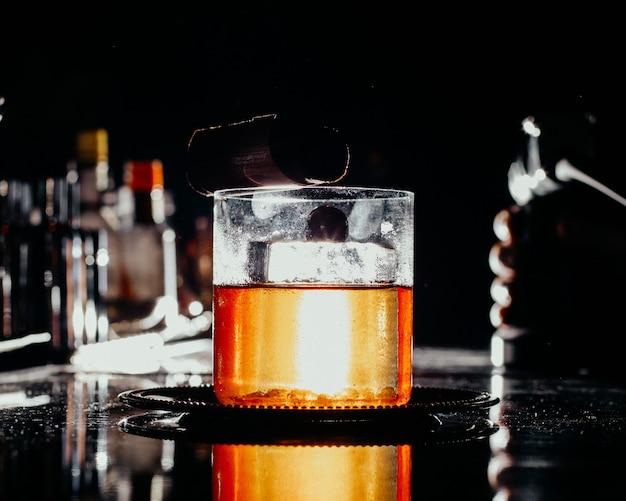 Вид спереди ледяной напиток в маленьком стакане на темном столе в баре пить сок, алкоголь, вода, бар Бесплатные Фотографии