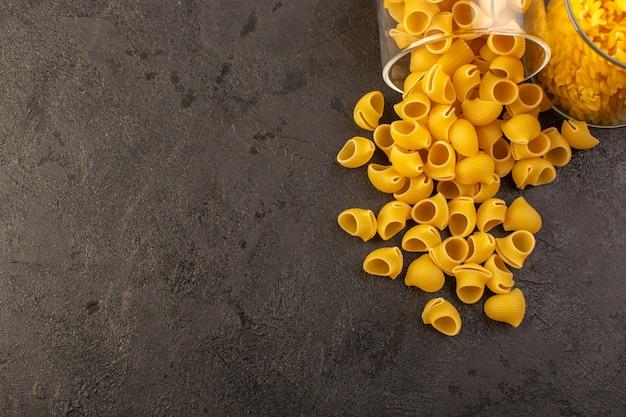 暗い背景のイタリアのパスタ料理の食事に分離されたボウルの内側正面イタリア乾燥パスタ黄色生 無料写真