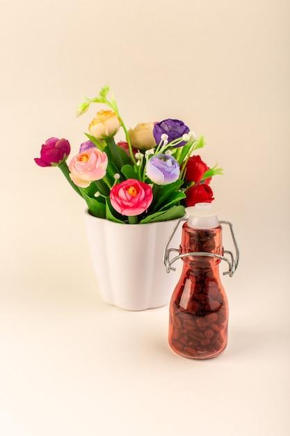 ピンクのテーブルコーヒー色の花の種にコーヒーと花が付いている正面図瓶 無料写真