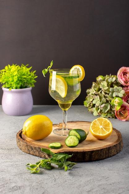 ガラスレモンストロー木製の机と灰色の背景カクテルドリンクフルーツの内側正面レモンカクテル新鮮な冷たい飲み物 無料写真