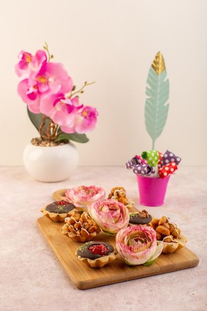 ピンクの机の上の花と正面の小さなチョコレートケーキ 無料写真