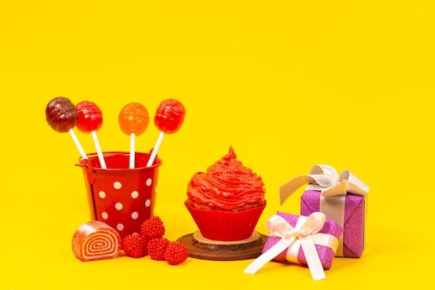 正面ロリポップと黄色、色砂糖ビスケットのマーマレードと紫のギフトボックスとケーキ 無料写真