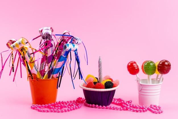 Леденцы на палочке и мармелад в маленьких ведерках, вид спереди, вместе со свистками на день рождения на розовом сладком сахаре Бесплатные Фотографии