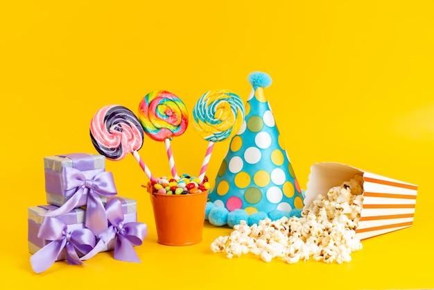 Леденцы на палочке спереди и попкорн вместе с синим колпачком фиолетовые подарочные коробки и конфеты на желтом Бесплатные Фотографии