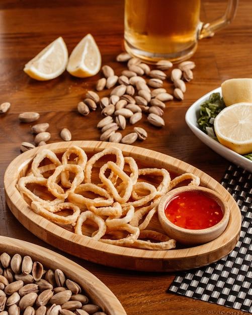 Луковые кольца с пивом и соусом из арахиса на коричневом деревянном столе Бесплатные Фотографии