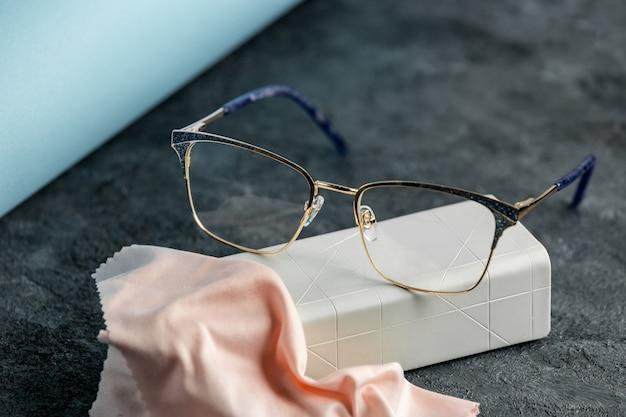 Оптические очки переднего вида на сером столе вместе с кремовой тканью для чистки изолировали зрение глазами Бесплатные Фотографии