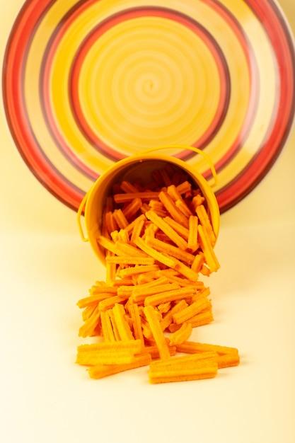 Макаронные изделия спереди в корзине сформировали оранжевое сырье внутри желтой корзины на кремовой пасте Бесплатные Фотографии