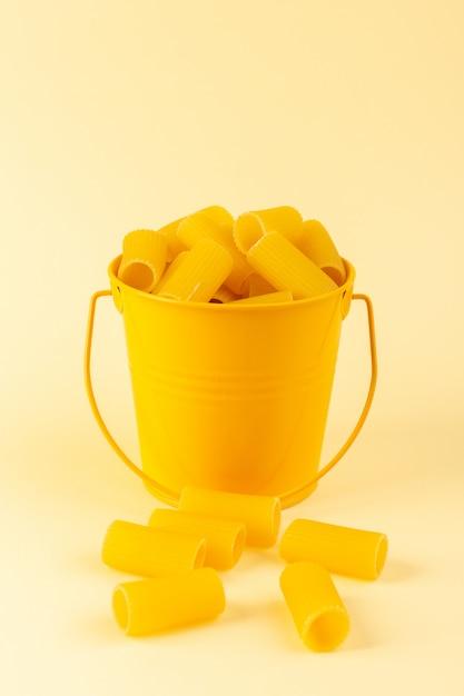 バスケットの中の正面図パスタは、クリーム色の背景に黄色のバスケットの内側に生を形成しました。食事食品イタリアンスパゲッティ 無料写真
