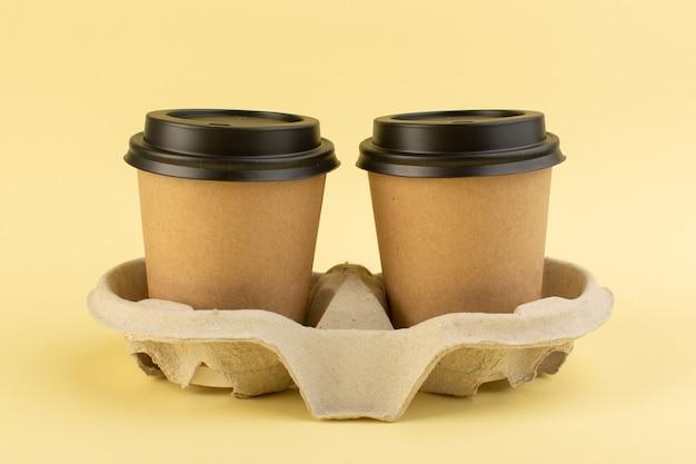 正面のプラスチック製のコーヒーカップの配達コーヒーの黄色のテーブルコーヒードリンク配達 無料写真
