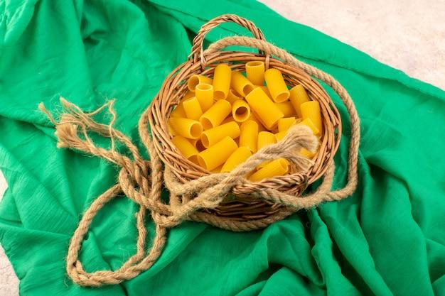 Вид спереди сырые итальянские макароны, желтые внутри маленькой корзины вместе с веревками на зеленой ткани Бесплатные Фотографии