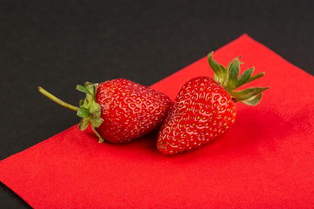 正面図の赤いイチゴは、テクスチャの赤と黒の背景のベリーにジューシーなまろやかな分離 無料写真