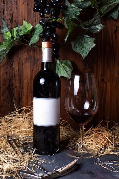 Вид спереди бутылка красного вина красного вина вместе с черным виноградом и зелеными листьями, изолированные на сером столе алкогольный напиток винзавод Бесплатные Фотографии