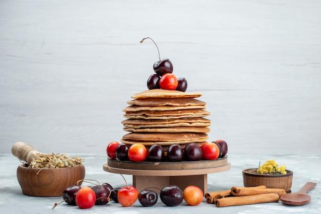 ライトデスクケーキフルーツのチェリーとシナモンの丸いパンケーキの正面図 無料写真