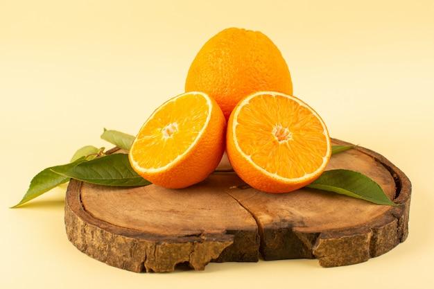 Вид спереди нарезанный апельсин и целые с зелеными листьями на деревянном коричневом столе изолировал свежую сочную спелую на сливках Бесплатные Фотографии