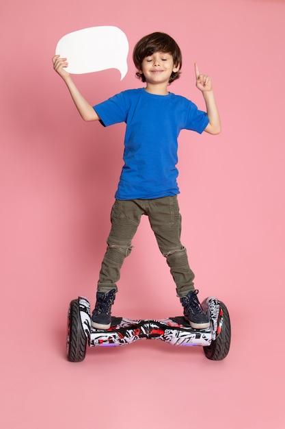 Улыбающийся мальчик спереди в синей футболке и брюках цвета хаки, едущий на сегвее на розовом полу Бесплатные Фотографии