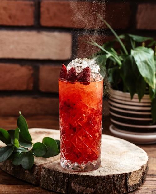 Клубничный коктейль с кубиками льда на коричневом деревянном столе, вид спереди, фруктовый коктейль jucie Бесплатные Фотографии