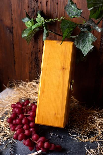 茶色の背景のワイナリーフルーツ果実に赤いブドウと緑の葉と共に閉じた正面黄色ボックス 無料写真