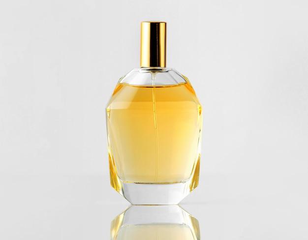Вид спереди желтый аромат в бутылке с золотой крышкой на белой стене Бесплатные Фотографии