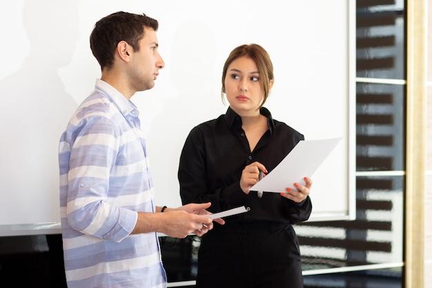 若い女性が机の上のグラフィックについて議論する若い男と一緒に黒いシャツを着た正面の若い魅力的な実業家 無料写真