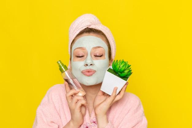 化粧クリーナースプレーと小さな植物を保持しているピンクのバスローブの正面の若い美しい女性 無料写真