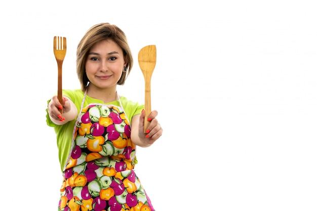 白い背景の家のクリーニングキッチンに笑みを浮かべて木製キッチンアプライアンスを保持している緑のシャツカラフルなケープの正面の若い美しい主婦 無料写真