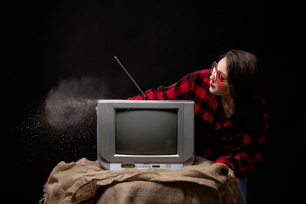 ほこりを吹き出す小さなテレビの近くの赤いサングラスの市松模様の赤黒シャツの正面の若い美しい女性 無料写真