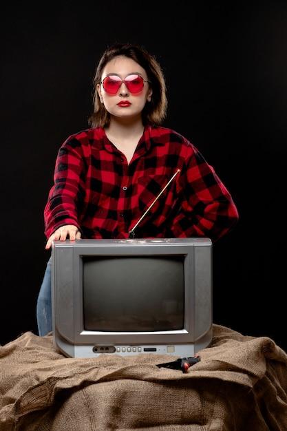 小さなテレビの近くの赤いサングラスの市松模様の赤黒シャツの正面の若い美しい女性 無料写真