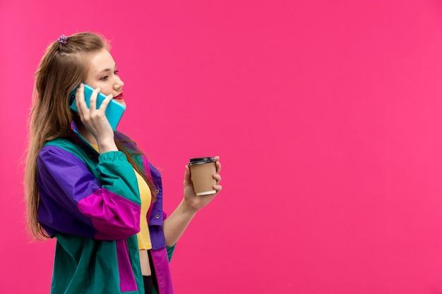 Вид спереди молодая красивая дама в красочной куртке оранжевого цвета рубашки черные брюки, улыбаясь, разговаривает по телефону, держа кофе Бесплатные Фотографии