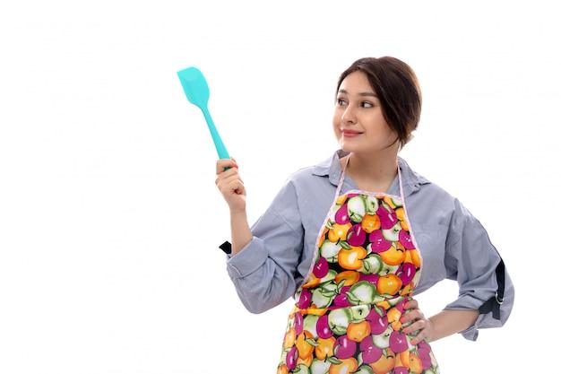 Вид спереди молодая красивая дама в светло-голубой рубашке и красочной накидке, думая, что держит синий кухонный прибор улыбается Бесплатные Фотографии