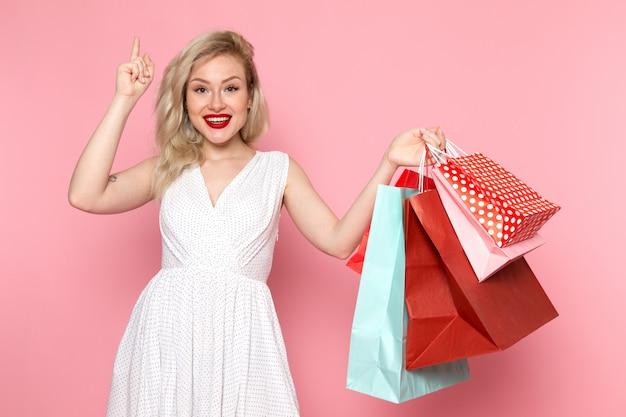 Вид спереди молодая красивая дама в белом платье держит пакеты покупок Бесплатные Фотографии