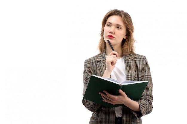 白いtシャツの黒のジーンズと白の思考を書き留めて緑の本を保持しているコートの正面の若い美しい女性 無料写真