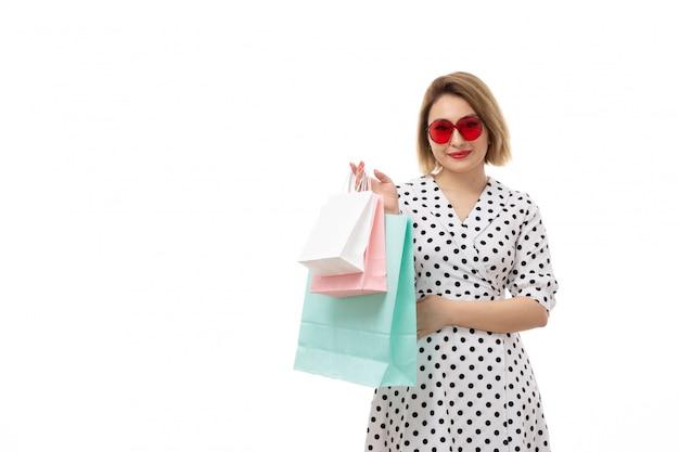 Вид спереди молодая красивая женщина в черно-белом платье в горошек в красных очках держит пакеты с покупками позирует Бесплатные Фотографии