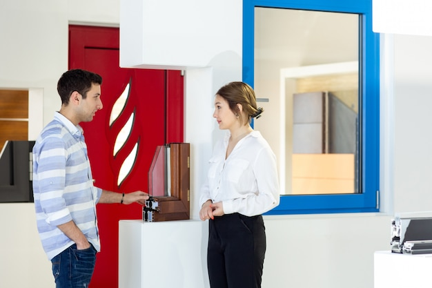 Вид спереди молодая красивая женщина в белой рубашке черных брюк вместе с молодым человеком, что-то обсуждали во время дневного строительства работы Бесплатные Фотографии