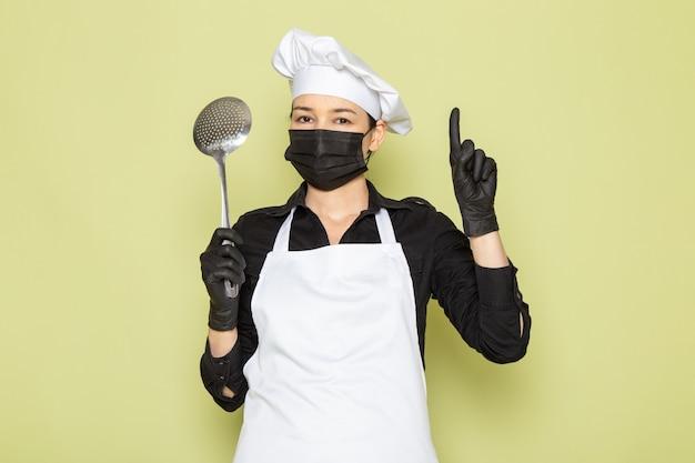 大きな銀のスプーンを保持している黒い手袋黒いマスクで黒いシャツ白いコック岬白い帽子で正面の若い女性料理人 無料写真