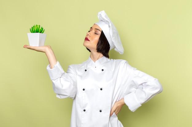 白いクックスーツと緑の壁に緑の植物を保持しているキャップで正面の若い女性クック女性作業食品料理色 無料写真