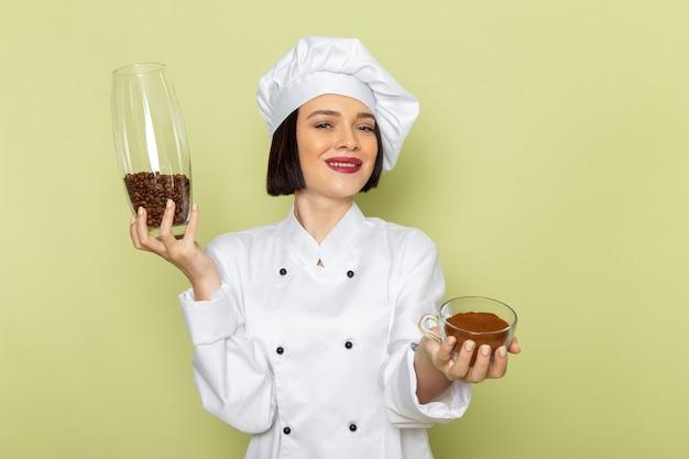 緑の壁の女性作業食品の色に白いクックスーツとコーヒーの種子が付いている瓶を保持しているキャップで正面の若い女性クック 無料写真