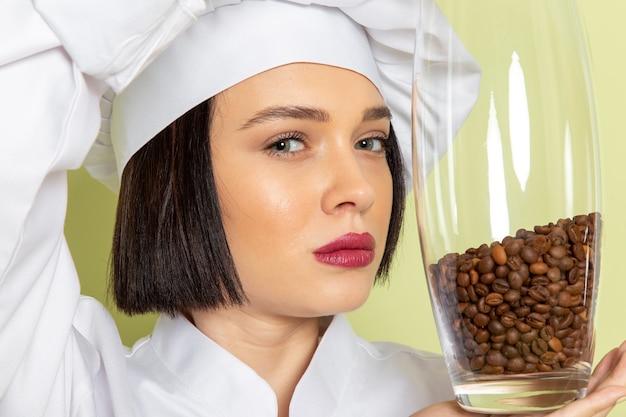 白いクックスーツと緑の壁の女性の種子にコーヒーの種子が付いている瓶を保持しているキャップで正面の若い女性クック食品料理色 無料写真