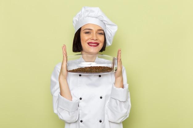 白いクックスーツと緑の壁に笑みを浮かべてコーヒーの種子が付いている瓶を保持しているキャップで若い女性クック正面女性作業食品料理色 無料写真