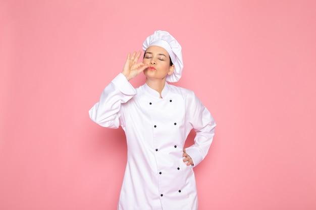 白いクックスーツホワイトキャップ笑顔のおいしい看板をポーズ笑顔で正面の若い女性クック 無料写真