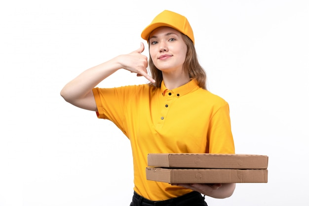 Вид спереди молодая женщина-курьер работница службы доставки еды, держа коробки для пиццы и показывая телефонный разговор знак на белом Бесплатные Фотографии