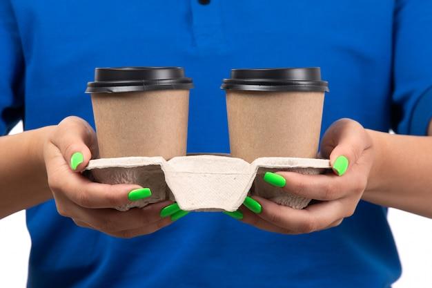 コーヒーカップを保持している青い制服を着た正面若い女性宅配便 無料写真