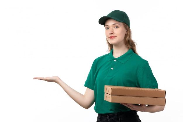 Молодая женщина-курьер в зеленой форме, держащая коробки для доставки пиццы, показывает ее пустую ладонь, вид спереди Бесплатные Фотографии