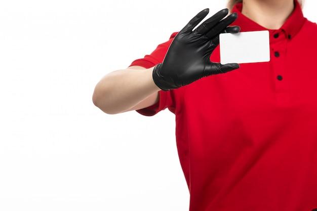 白い背景の均一なサービスを提供する上で白いカードを保持している赤いシャツ黒革手袋の正面の若い女性宅配便 無料写真