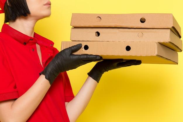 Вид спереди молодой женщины курьер в красной форме черные перчатки и красной кепке, держа еду коробки Бесплатные Фотографии