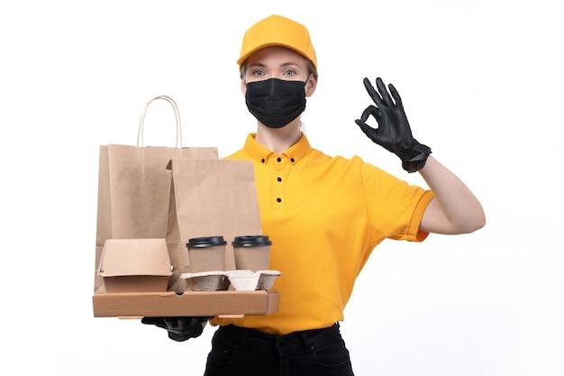 Вид спереди молодая женщина-курьер в желтой униформе, черные перчатки и черная маска, держащая пакеты для доставки еды из кофейных чашек Бесплатные Фотографии