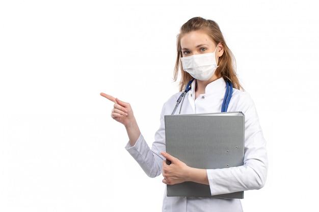 白の灰色のファイルを保持している白い防護マスクを着ている聴診器で白い医療スーツの正面の若い女性医師 無料写真