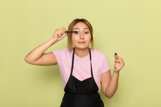 Вид спереди молодая женщина-парикмахер в розовой футболке и черной накидке делает макияж на зеленом Бесплатные Фотографии