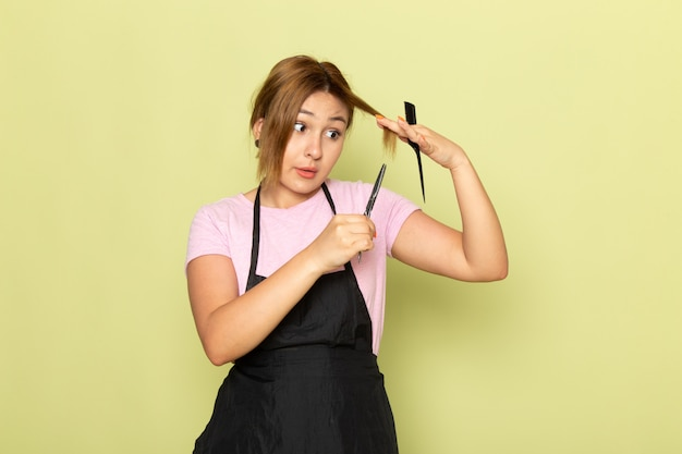 Молодая женщина-парикмахер в розовой футболке и черной накидке, держащая кисть и ножницы, фиксирует волосы на зеленом, вид спереди Бесплатные Фотографии