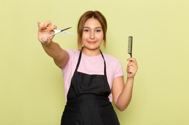Молодая женщина-парикмахер в розовой футболке и черной накидке, держащая кисть и ножницы, улыбается на зеленом фоне, вид спереди Бесплатные Фотографии